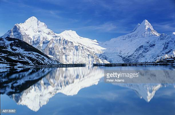 switzerland, swiss alps, mountains reflected in lake water - swiss alps stock pictures, royalty-free photos & images