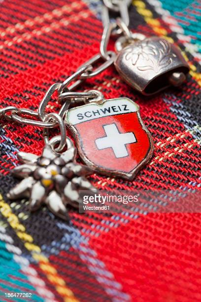 Switzerland, Swiss flag on charm bracelet with cow bell and edelweiss