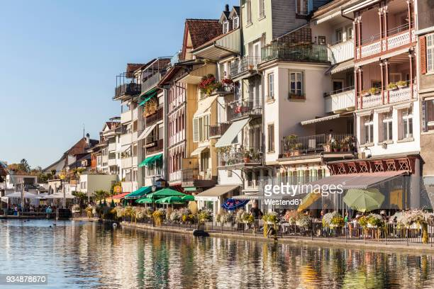 switzerland, thun, row of houses with pavement cafes and restaurants at riverside of aare - ベルンカントン ストックフォトと画像