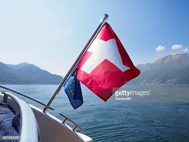 Switzerland, Ticino, Lago Maggiore, boat with Swiss and EU flag on lake