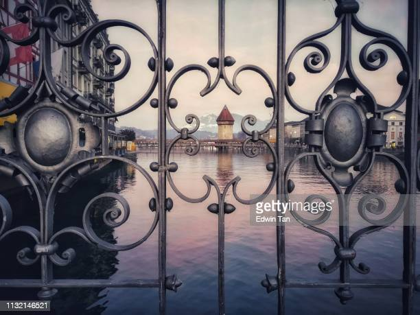 switzerland town bridge view through a fence during sunset - zurich stock pictures, royalty-free photos & images