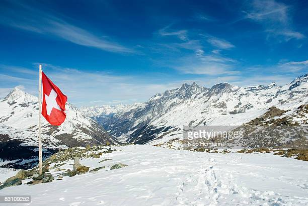 Switzerland, Wallis, The Alps, Swiss flag on snowcapped mountain
