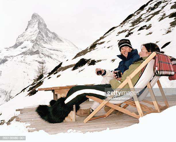 Switzerland, Zermatt, couple in deck chairs drinking, by Matterhorn