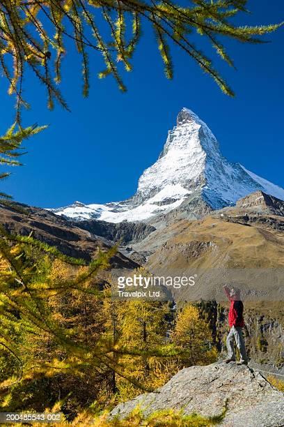 Switzerland, Zermatt, Matterhorn, man standing, arm up, side view