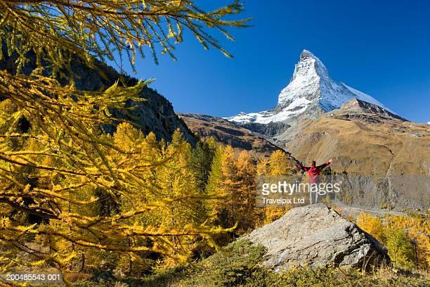 Switzerland, Zermatt, Matterhorn, man standing, arms out, rear view