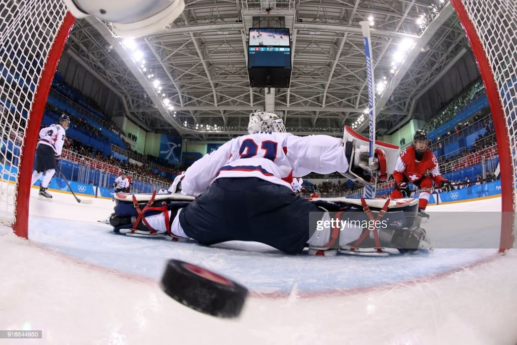 TOPSHOT - Switzerland's Alina Muller (25) scores a goal against Unified Korea's goalie Shin So-jung (31) during the women's preliminary round ice hockey match between Switzerland and the Unified Korean team during the Pyeongchang 2018 Winter Olympic Games at the Kwandong Hockey Centre in Gangneung on February 10, 2018. /