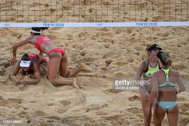 Switzerland's Anouk Verge-Depre and partner Joana Heidrich reach for the ball, as Germany's Julia Sude talks to partner Karla Borger, in their...