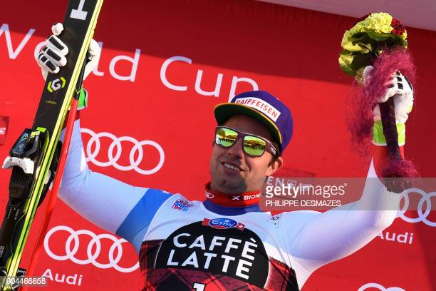 Switzerland's Beat Feuz celebrates on the podium after winning the Downhill race at the FIS Alpine Skiing World Cup in Wengen on January 13 2018 /...