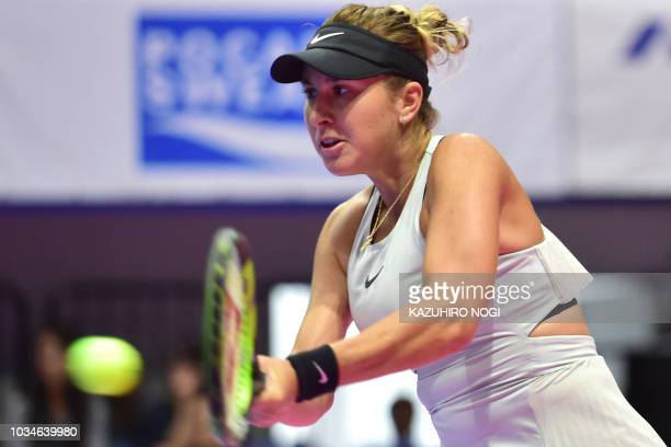 Switzerland's Belinda Bencic hits a return against Spain's Garbine Muguruza during their women's singles first round match at the Pan Pacific Open...