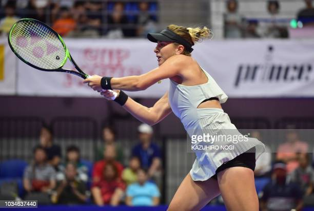 Switzerland's Belinda Bencic returns a shot against Spain's Garbine Muguruza during their women's singles first round match at the Pan Pacific Open...