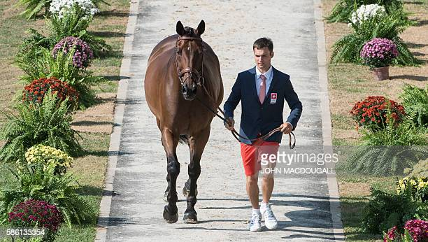Switzerland's Ben Vogg leads Noe des Vatys to a trot during the first horse inspection of the Equestrian's Eventing phase during the 2016 Rio Olympic...