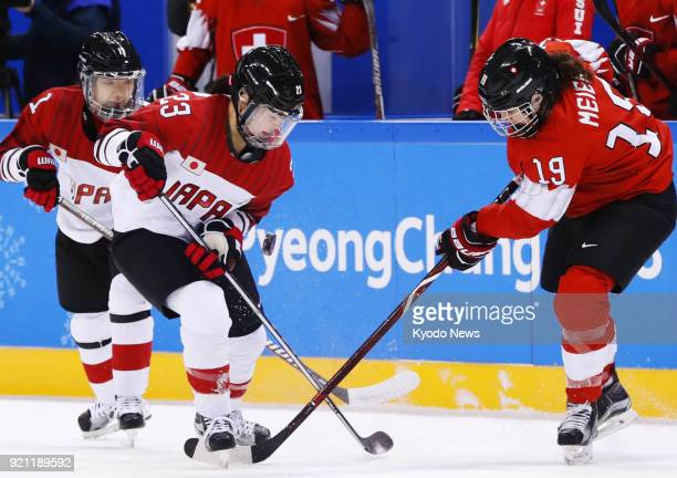 Switzerland's Christine Meier and Ami Nakamura of Japan vie for the puck during the first period of the women's ice hockey game for fifth place at...