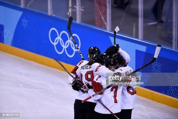 TOPSHOT Switzerland's Christine Meier Lara Stalder Switzerland's Alina Muller celebrate winning the women's preliminary round ice hockey match...