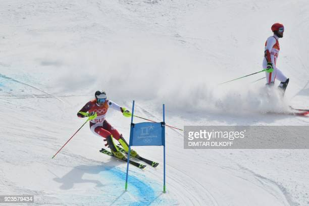 Switzerland's Daniel Yule advances to the finishline as Austria's Marco Schwarz stops competing in the Alpine Skiing Team Event big final at the...