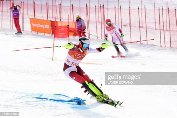 TOPSHOT Switzerland's Daniel Yule advances to the finishline as Austria's Marco Schwarz stops competing in the Alpine Skiing Team Event big final at...