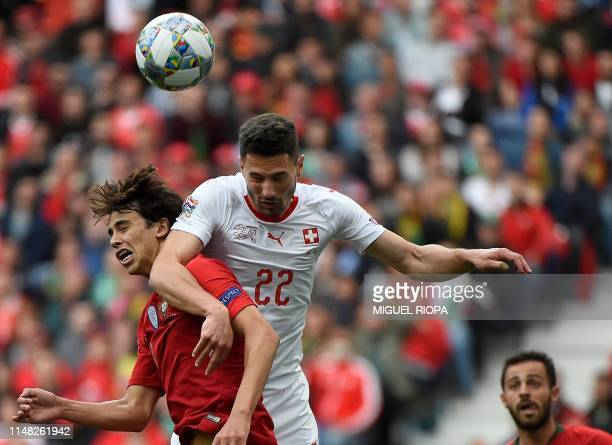 TOPSHOT Switzerland's defender Fabian Schar heads the ball with Portugal's midfielder Joao Felix during the UEFA Nations League semifinal football...