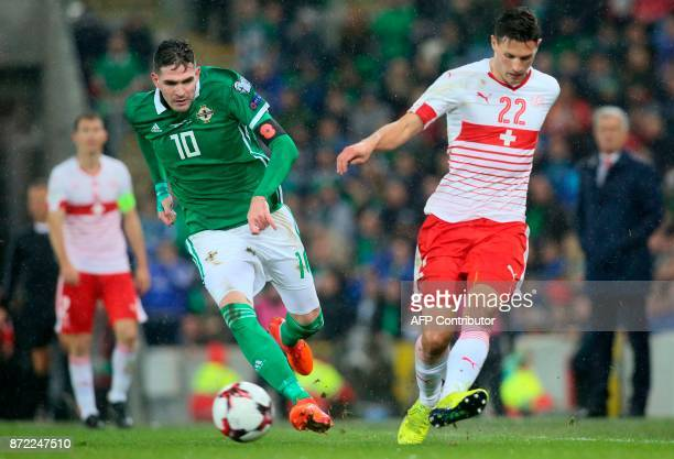 Switzerland's defender Fabian Schar plays the ball ahead of Northern Ireland's striker Kyle Lafferty during the FIFA 2018 World Cup qualifier second...