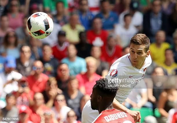 TOPSHOT Switzerland's defender Johan Djourou and Poland's forward Arkadiusz Milik vie for the ball during the Euro 2016 round of sixteen football...