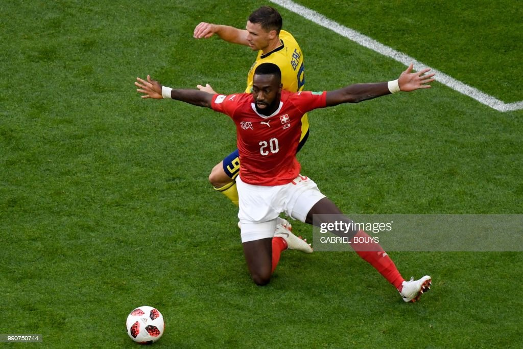 TOPSHOT - Switzerland's defender Johan Djourou fights for the ball with Sweden's forward Marcus Berg (top) during the Russia 2018 World Cup round of 16 football match between Sweden and Switzerland at the Saint Petersburg Stadium in Saint Petersburg on July 3, 2018. (Photo by GABRIEL BOUYS / AFP) / RESTRICTED