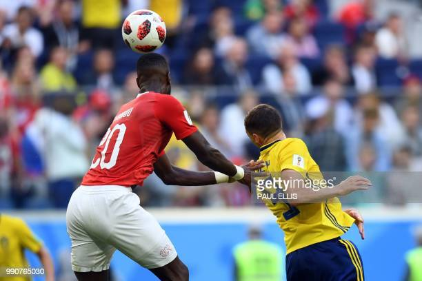 Switzerland's defender Johan Djourou heads the ball with Switzerland's forward Haris Seferovic during the Russia 2018 World Cup round of 16 football...