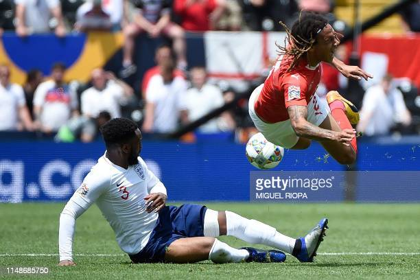 Switzerland's defender Kevin Mbabu is tackled by England's defender Danny Rose during the UEFA Nations League third place playoff football match...