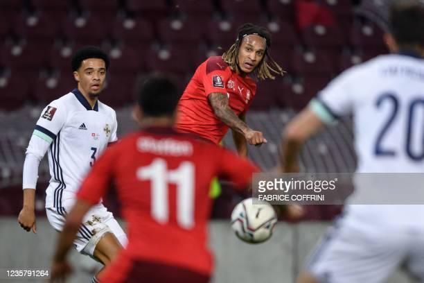 Switzerland's defender Kevin Mbabu kicks the ball next to Northern Ireland's defender Jamal Lewis during FIFA World Cup Qatar 2022 qualification...