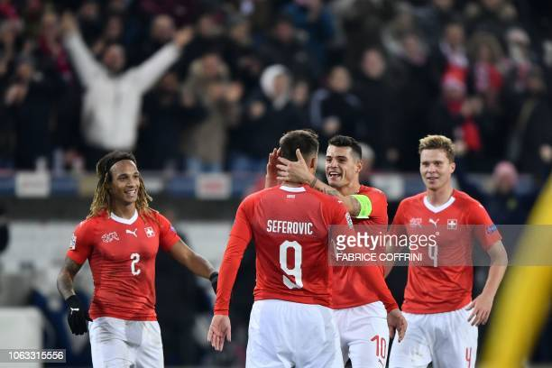 Switzerland's defender Kevin Mbabu team mates forward Haris Seferovic midfielder Granit Xhaka and defender Nico Elvedi reacts after Seferovic scores...