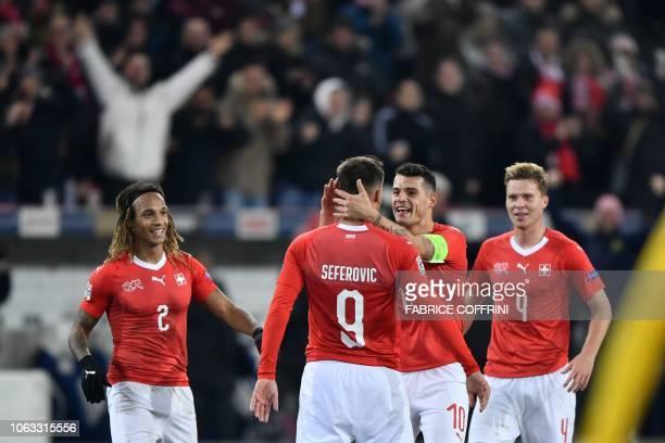 Switzerland's defender Kevin Mbabu, team mates forward Haris Seferovic, midfielder Granit Xhaka and defender Nico Elvedi reacts after Seferovic...