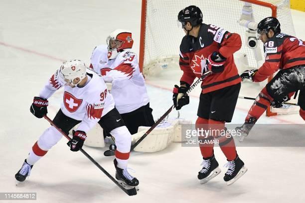 Switzerland's defender Lukas Frick and Switzerland's goalkeeper Leonardo Genoni defend their goal against Canada's forward Kyle Turris aand Canada's...