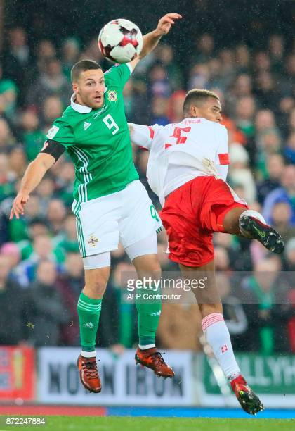Switzerland's defender Manuel Akanji jumps with Northern Ireland's striker Conor Washington during the FIFA 2018 World Cup qualifier second round...