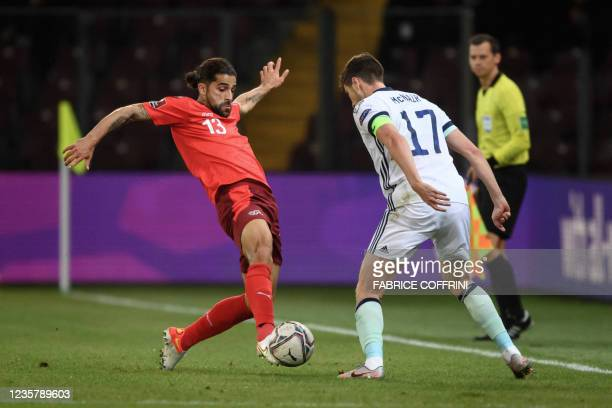 Switzerland's defender Ricardo Rodriguez and Northern Ireland's midfielder Patrick McNair vie for the ball during the FIFA World Cup 2022 Group C...