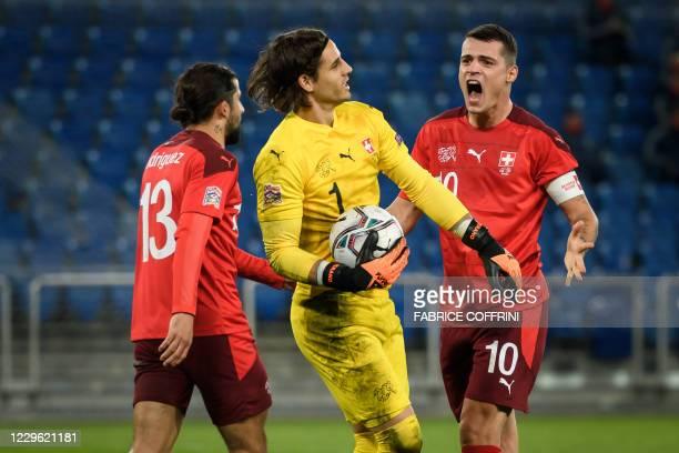 Switzerland's defender Ricardo Rodriguez and Switzerland's midfielder Granit Xhaka congratulate Switzerland's goalkeeper Yann Sommer after he saved a...
