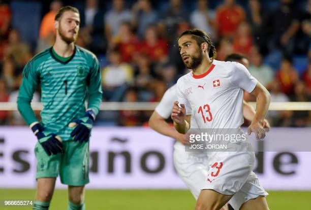 Switzerland's defender Ricardo Rodriguez celebrates a goal beside Spain's goalkeeper David de Gea during the international friendly football match...
