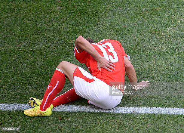Switzerland's defender Ricardo Rodriguez holds his hurt back during a Group E football match between Switzerland and Ecuador at the Mane Garrincha...