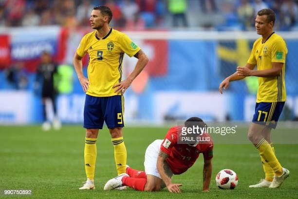 Switzerland's defender Ricardo Rodriguez kneels on the ground past Switzerland's forward Haris Seferovic and Sweden's midfielder Viktor Claesson...