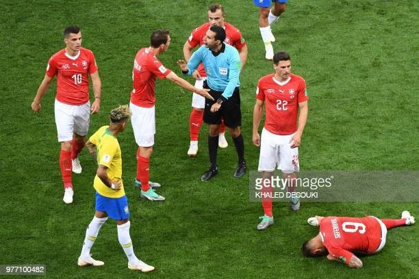 Switzerland's defender Stephan Lichtsteiner argues with referee Cesar Ramos as Switzerland's forward Haris Seferovic reacts during the Russia 2018...