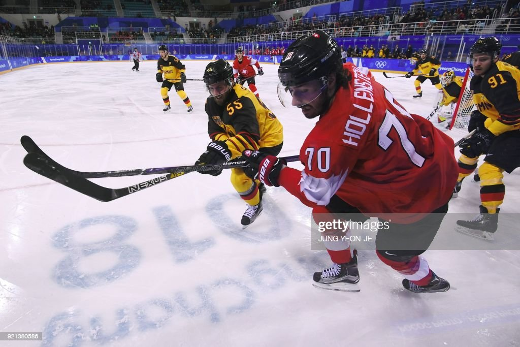 Switzerland's Denis Hollenstein (2nd R) and Germany's Felix Schutz (C) fight for the puck in the men's play-offs qualifications ice hockey match between Switzerland and Germany during the Pyeongchang 2018 Winter Olympic Games at the Kwandong Hockey Centre in Gangneung on February 20, 2018. / AFP PHOTO / Jung Yeon-je