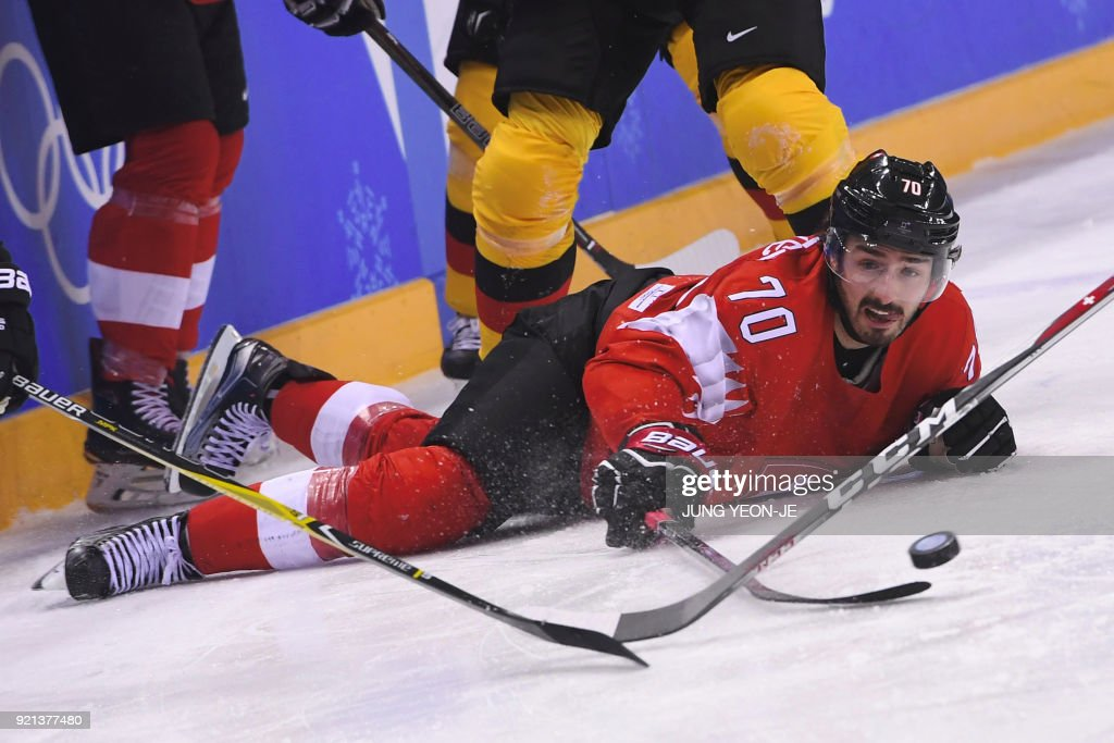 TOPSHOT - Switzerland's Denis Hollenstein looks at the puck in the men's play-offs qualifications ice hockey match between Switzerland and Germany during the Pyeongchang 2018 Winter Olympic Games at the Kwandong Hockey Centre in Gangneung on February 20, 2018. / AFP PHOTO / Jung Yeon-je