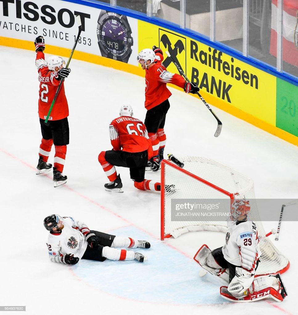 Switzerland's Enzo Corvi (top R) celebrates with his teammates after scoring past Austria's goalie Bernhard Starkbaum (R) the game-winning goal at overtime to win the group A match Switzerland vs Austria of the 2018 IIHF Ice Hockey World Championship at the Royal Arena in Copenhagen, Denmark, on May 5, 2018.