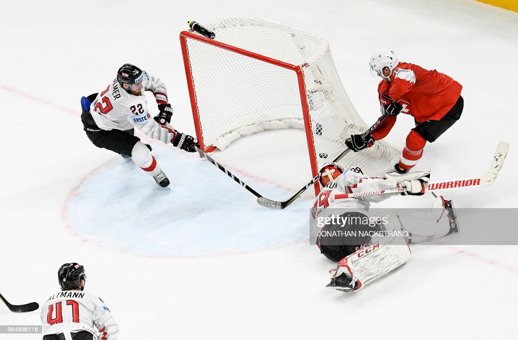 Switzerland's Enzo Corvi (R) strikes behind Austria's goalie Bernhard Starkbaum (2nd R) to score the game-winning goal at overtime during the group A match Switzerland vs Austria of the 2018 IIHF Ice Hockey World Championship at the Royal Arena in Copenhagen, Denmark, on May 5, 2018.