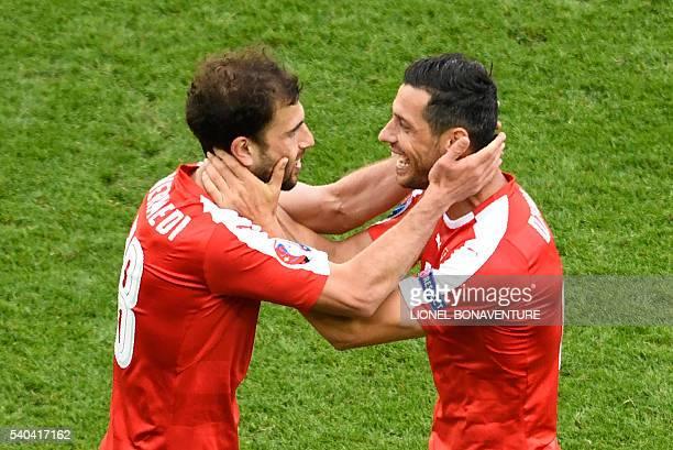 Switzerland's forward Admir Mehmedi celebrates with Switzerland's midfielder Blerim Dzemaili after scoring a goal during the Euro 2016 group A...