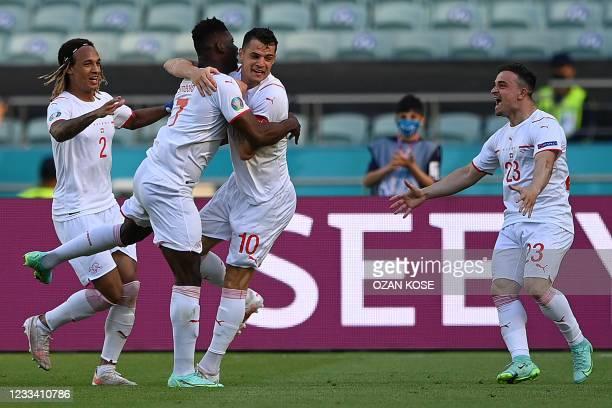 Switzerland's forward Breel Embolo celebrates his opening goal with Switzerland's defender Kevin Mbabu , Switzerland's midfielder Granit Xhaka and...