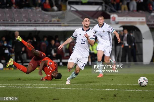 Switzerland's forward Breel Embolo falls next to Northern Ireland's midfielder Jordan Thompson and Northern Ireland's defender Daniel Ballard during...