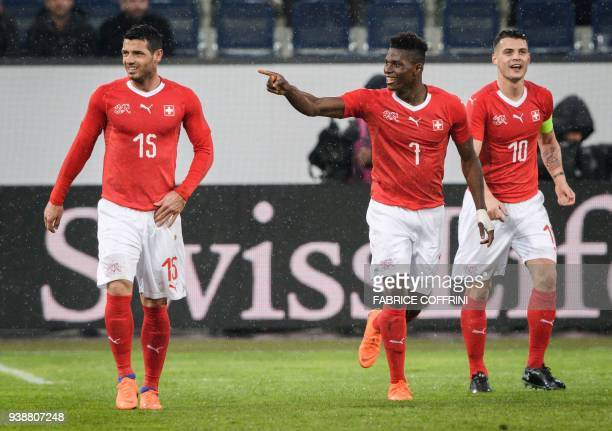 Switzerland's forward Breel Embolo reacts between teammates midfielder Blerim Dzemaili and midfielder Granit Xhaka after scoring a goal during the...