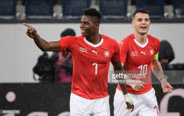 Switzerland's forward Breel Embolo reacts next toteammates midfielder Granit Xhaka after scoring a goal during the international friendly football...