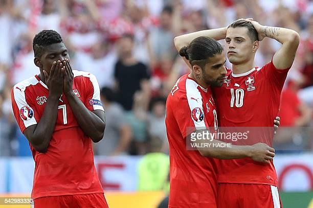 TOPSHOT Switzerland's forward Breel Embolo Switzerland's defender Ricardo Rodriguez and Switzerland's midfielder Granit Xhaka react after the Euro...