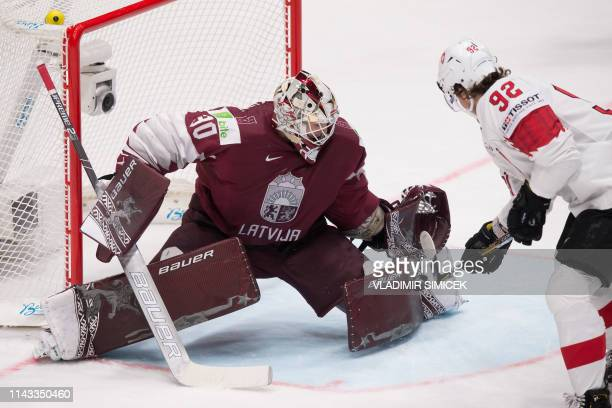 Switzerlands forward Gaetan Haas vies with Latvia's goalkeeper Elvis Merzlikins during the IIHF Men's Ice Hockey World Championships Group B match...