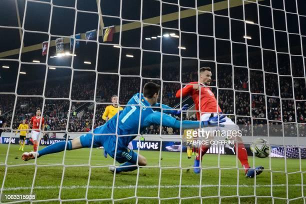 Switzerland's forward Haris Seferovic scores his team's second goal against Belgium's goalkeeper Thibaut Courtois during the UEFA Nations League...