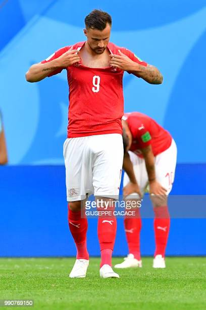 Switzerland's forward Haris Seferovic tears his jersey after the team lost the Russia 2018 World Cup round of 16 football match between Sweden and...