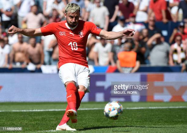 Switzerland's forward Josip Drmic misses a penalty kick during the penalty shootout after the UEFA Nations League third place football match between...